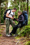 Backpack Couple. A couple on a backpacking camping trip looking at a map stock images
