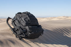 Backpack in desert Royalty Free Stock Image