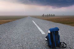 Backpack on empty road Royalty Free Stock Images