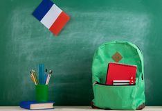 Backpack, flag of the France, book and school supplies on the background of the blackboard. Learning languages concept - green backpack, flag of the France, book stock photo