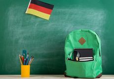 Backpack, flag of the Germany, school supplies and notebooks on the background of the blackboard. Learning languages concept - green backpack, flag of the royalty free stock photography
