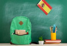 Backpack, flag of the Spain, books and school supplies on the background of the blackboard. Learning languages concept - green backpack, flag of the Spain, books royalty free stock photos