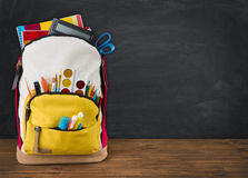 Backpack full of school supplies over black school board background.  Stock Photography
