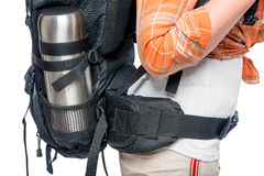 Backpack full of tourists at the waist with a thermos Royalty Free Stock Image
