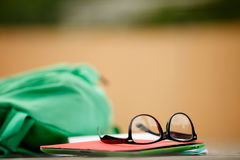 Backpack with glasses and book lying on wooden board. Blurred background.Accessories for student Royalty Free Stock Images