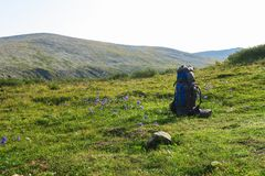 Backpack on the grass meadow with mountains on the background. Summer hiking motivational image. Space for text royalty free stock images