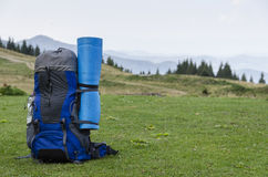 Backpack on grass. Mountains top Stock Photography