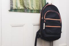 A backpack hanging on a door. Ready to go back to school Stock Photos