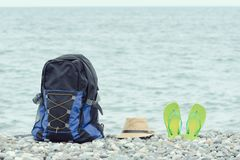 Backpack, hat and flip-flops on the pebble beach. Sea in the background.  stock photography