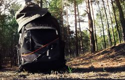 Backpack in forest. Backpack with hat, glasses and flashlight laying on forest ground with daylight forest background Stock Photo