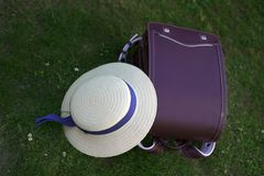 Backpack and hat lie on the grass. School backpack and hat with ribbon lie on green grass Royalty Free Stock Photo