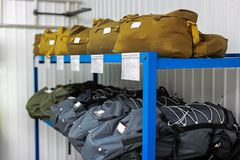A backpack of lifeguards and firefighters with personal belongings and bags with gas masks are on the shelves in the warehouse royalty free stock photos