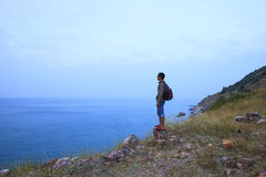 Backpack man standing on rock mountain and looking to ocean use Royalty Free Stock Photography