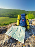 Backpack and map in mountain. Royalty Free Stock Photography