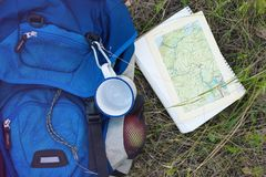 Backpack and map. A backpack, a mug, a notepad and a map are lying on the grass. Tourist equipment. The apple lies in the pocket of the backpack. Walk in the royalty free stock photos