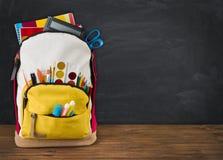 Backpack in pieno dei rifornimenti di scuola sopra il fondo nero del consiglio scolastico