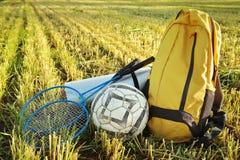 Backpack, raquetes para o badbotton, bola, esteira do piquenique Ir em umas férias de verão relaxa o feriado Fotografia de Stock Royalty Free