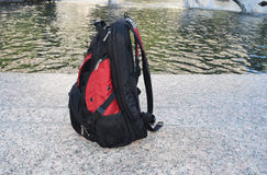 Backpack ready to travel. Red and Black backpack on urban street near streaming water Stock Images