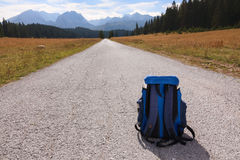 Backpack on the road leading into the mountains Stock Photo