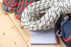 Backpack, rope and shoes for hiking in the mountains and forests on a wooden light background royalty free stock image