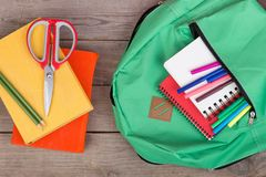 Backpack and school supplies: books, notepad, felt-tip pens, scissors. On brown wooden table royalty free stock photos