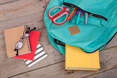 Backpack and school supplies: books, pencils, notepad, felt-tip pens, eyeglasses, scissors on wooden table