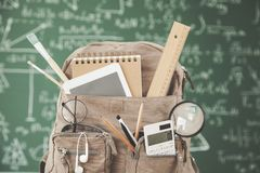 Backpack school with supplies in front of green chalkboard stock photography
