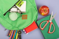 Backpack and school supplies: magnifying glass, notepad, felt-tip pens, eyeglasses, scissors, calculator, book, watch on blue pape. R background royalty free stock image