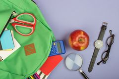 Backpack and school supplies: magnifying glass, notepad, felt-tip pens, eyeglasses, scissors, calculator, watch on blue paper back. Ground stock photography