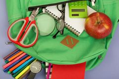 Backpack and school supplies: magnifying glass, notepad, felt-tip pens, eyeglasses, scissors, calculator, watch on blue paper back. Ground royalty free stock photo