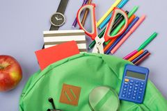 Backpack and school supplies: magnifying glass, notepad, felt-tip pens, eyeglasses, scissors, calculator, watch on blue paper back. Ground stock photos