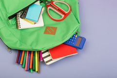 Backpack and school supplies: note pad, felt-tip pens, scissors, calculator on blue paper background. Backpack and school supplies: notepad, felt-tip pens stock photos