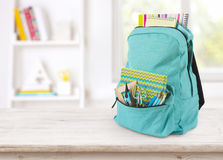 Backpack with school supplies on table over blurred educational interior royalty free stock images
