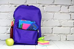 Backpack with school supplies and white brick background Stock Images
