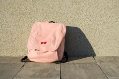 A backpack schoolgirl. Background gray solar wall royalty free stock photos