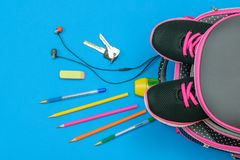 Backpack with sneakers and scattered school accessories and house keys on a blue table. Flat lay. Top view. Backpack with sneakers and scattered school stock photo