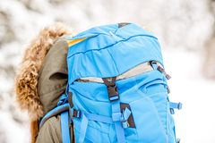 Backpack in the snowy forest. Close-up back view on the woman with blue backpack on the snowy forest background Royalty Free Stock Photo