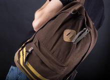 Backpack sulla spalla di un giovane sul nero Fotografie Stock Libere da Diritti