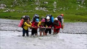 Backpack tourist crossing the mountaun stream river stock footage