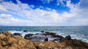 Backpack Tourist Sits on Rocky Beach Admires Scenery stock video