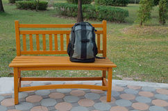 Backpack on wooden bench Stock Photography