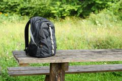 Backpack on wooden table royalty free stock photography