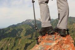 Backpacke della donna che fa un'escursione sulla scogliera del picco di montagna Fotografia Stock