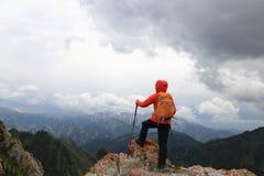 Backpacke della donna che fa un'escursione sulla scogliera del picco di montagna Immagini Stock Libere da Diritti