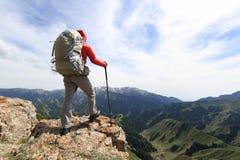 Backpacke della donna che fa un'escursione sulla scogliera del picco di montagna Fotografia Stock Libera da Diritti