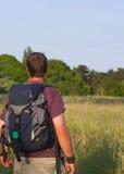 backpacker πεδίο ηλιόλουστο στοκ φωτογραφία