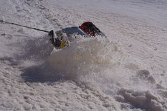 Backpacker που γλιστρά στο υγρό χιόνι και που πέφτει κάτω από μια κλίση Στοκ Φωτογραφία