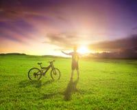 Backpacker που στέκεται δίπλα στο ποδήλατο με το υπόβαθρο ηλιοβασιλέματος Στοκ εικόνες με δικαίωμα ελεύθερης χρήσης