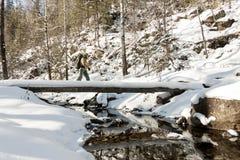 Backpacker девушки идя на мост над замороженным рекой в лесе зимы в горах Стоковая Фотография