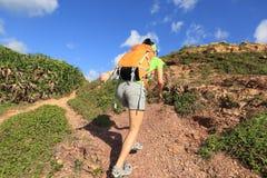 Backpacker женщины взбираясь на горной тропе взморья Стоковое фото RF